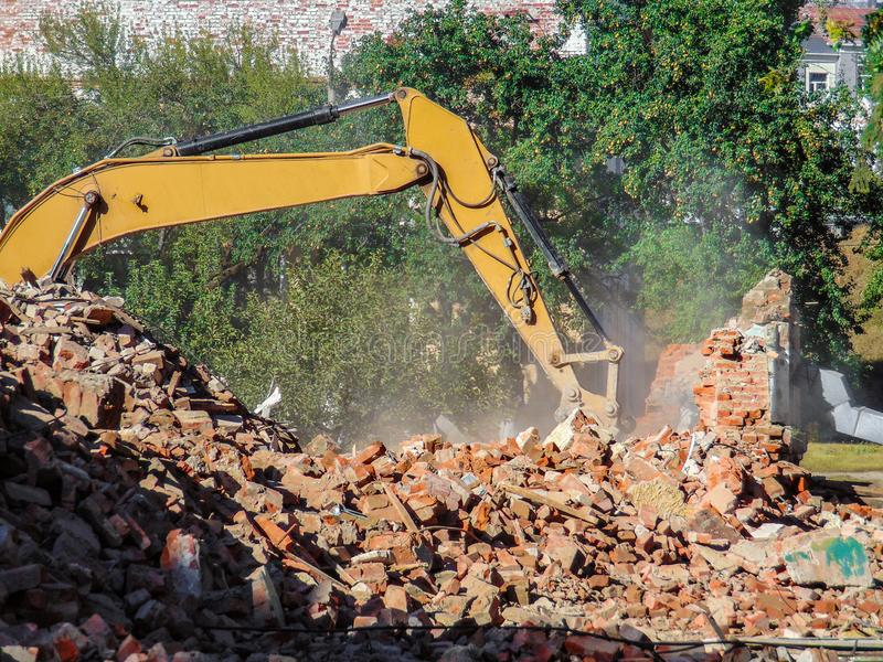 Dismantling a brick building with a bucket excavator. Ruins and remains of walls royalty free stock images
