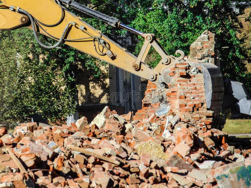 Dismantling a brick building with a bucket excavator. Ruins and remains of walls. Limited depth of field royalty free stock photos
