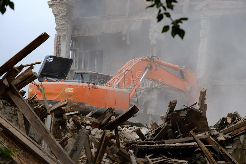 Dismantling of the building with a large excavator, with the destruction of a lot of dust. And debris stock photography
