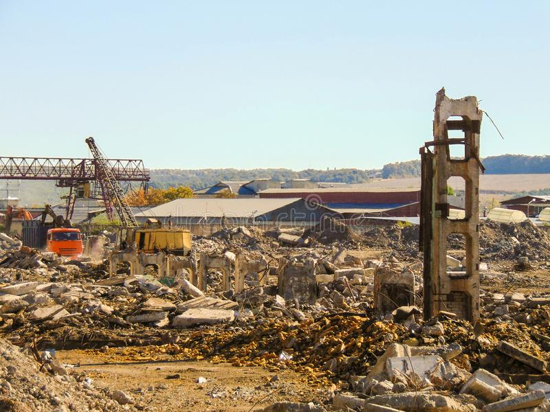 Dismantling of reinforced concrete constructions frame. Site area with the ruins of an industrial building royalty free stock image