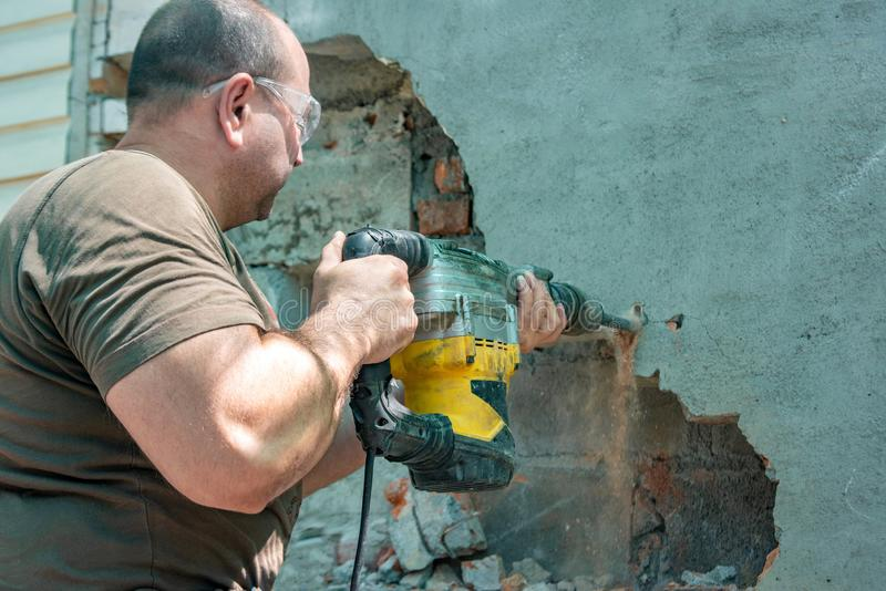 Dismantling walls and openings with an electric jackhammer. The worker in goggles performs repair work.  royalty free stock photos