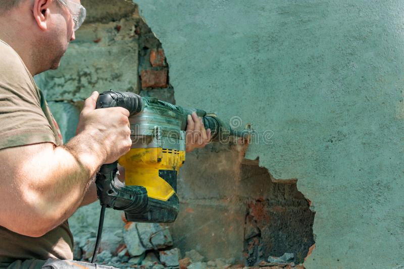 Dismantling walls and openings with an electric jackhammer. The worker in goggles performs repair work.  royalty free stock images