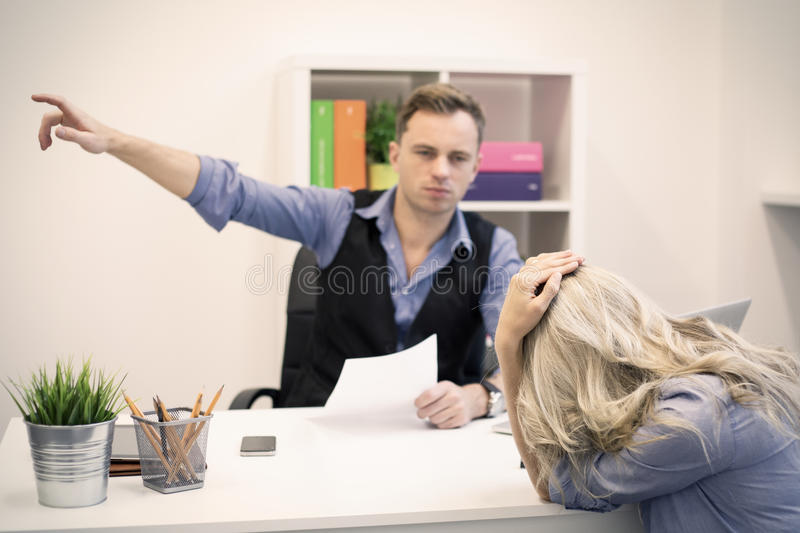 Dismissal, firing and sacking concept. Boss is showing doors to young unhappy female employee royalty free stock photography