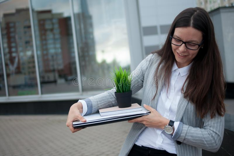 Dismissal from a large company. Economic crisis and problems with qualifications. A depressed young woman is sitting on the steps in front of the business royalty free stock image