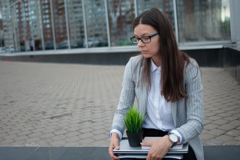 Dismissal from a large company. Economic crisis and problems with qualifications. A depressed young woman is sitting on the steps in front of the business royalty free stock photos