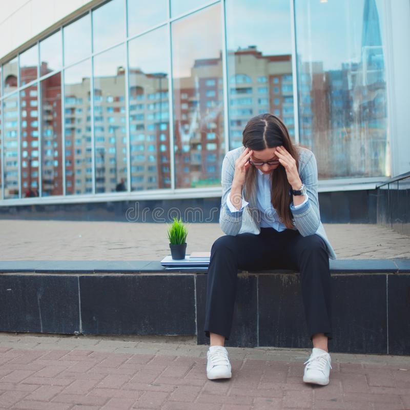 Dismissal from a large company. Economic crisis and problems with qualifications. A depressed young woman is sitting on the steps in front of the business royalty free stock photography