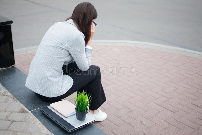 Dismissal from a large company. Economic crisis and problems with qualifications. A depressed young woman is sitting on the steps in front of the business stock photo