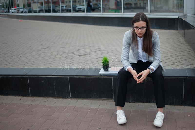 Dismissal from a large company. Economic crisis and problems with qualifications. A depressed young woman is sitting on the steps in front of the business stock image