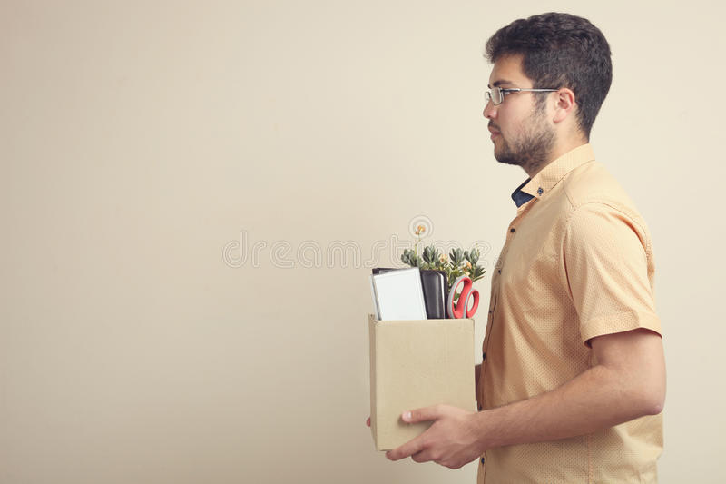 Dismissal from work. A man in a shirt is holding a box of his things on a neutral background. Concept dismissal royalty free stock image