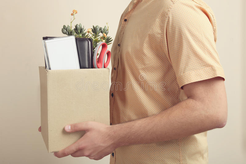 Dismissal from work. A man in a shirt is holding a box of his things on a neutral background. Concept dismissal stock photos