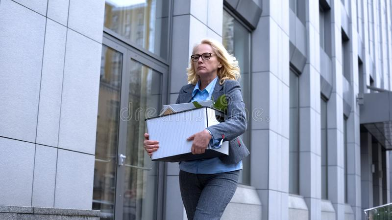 Dismissed female manager carrying stuff box leaving business center, career royalty free stock photo