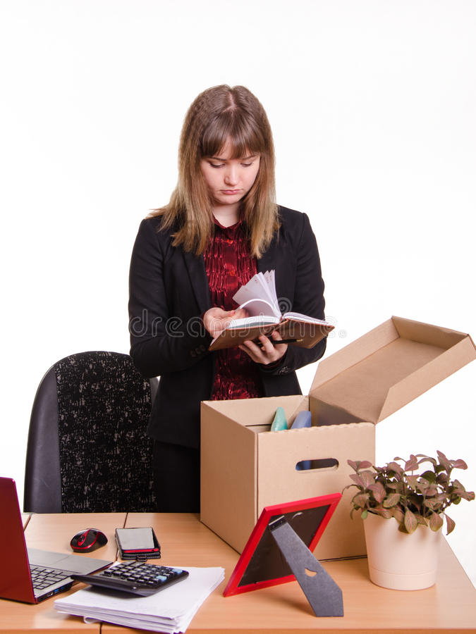 Dismissed girl in office goes through personal belongings. Woman fired from her job at the office and collect personal belongings in a box with a sad view stock images