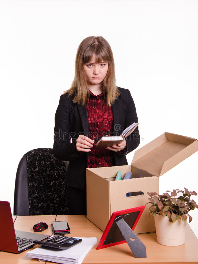 Dismissed girl puts personal belongings in office. Woman fired from her job at the office and collect personal belongings in a box with a sad view royalty free stock photography