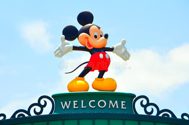 Disney icon mickey mouse. Large figurine of mickey mouse on the welcome banner with natural light blue sky background at disneyland, hong kong