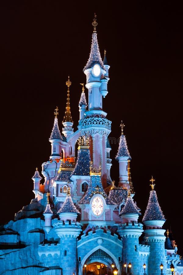 Disneyland Paris slott under julberömmar på natten royaltyfria foton