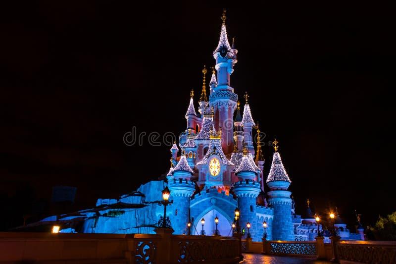 Disneyland Paris slott under julberömmar på natten arkivbilder
