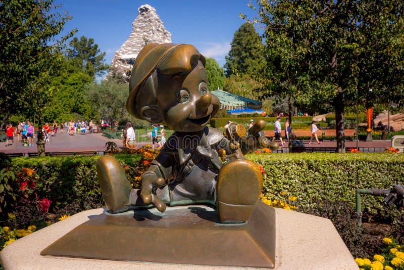 Disneyland Pinocchio Bronze Statue. The bronze Pinocchio as a `real boy` greets children to Disneyland. The Matterhorn mountain in the background stock photo