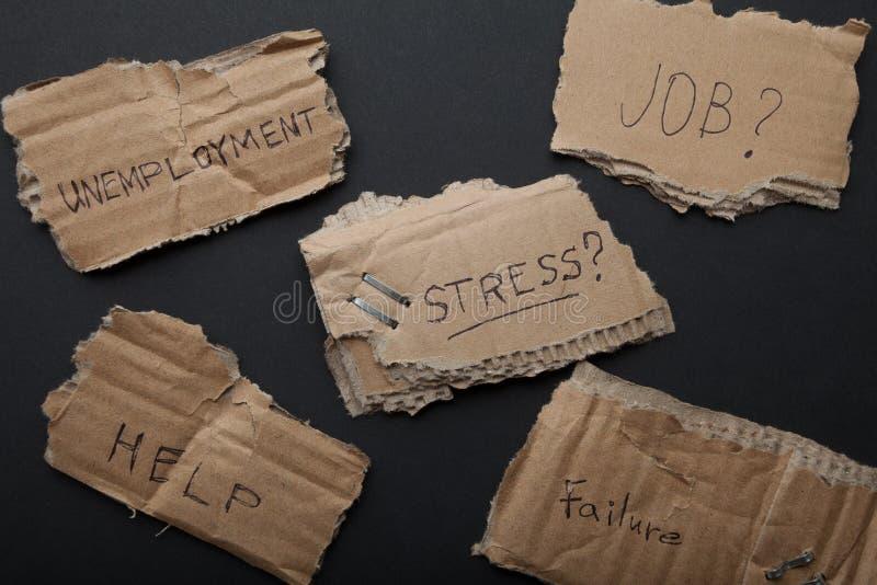 Disoccupazione, problemi, sforzo, aiuto, lavoro Iscrizioni sul cartone fotografie stock libere da diritti