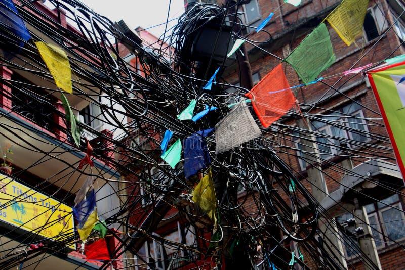 Disordine dei cavi e delle bandiere di preghiera a Kathmandu immagine stock
