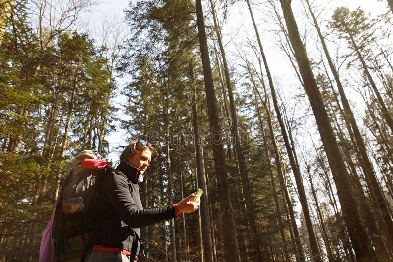 Disoriented hiker checking her phone for direction. Disoriented hiker checking her phone for GPS coordinates, being lost in the woods, looking for the right stock images