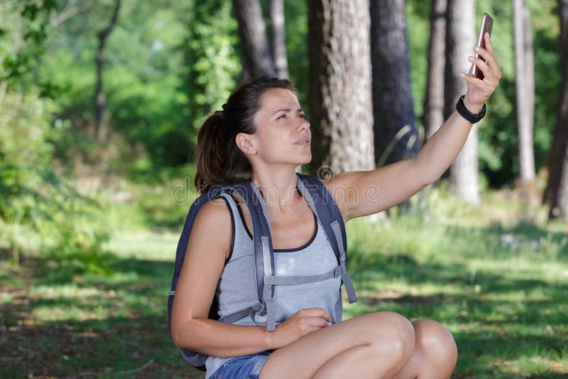 Disoriented hiker checking phone for gps coordinates. Disoriented hiker checking her phone for gps coordinates stock images