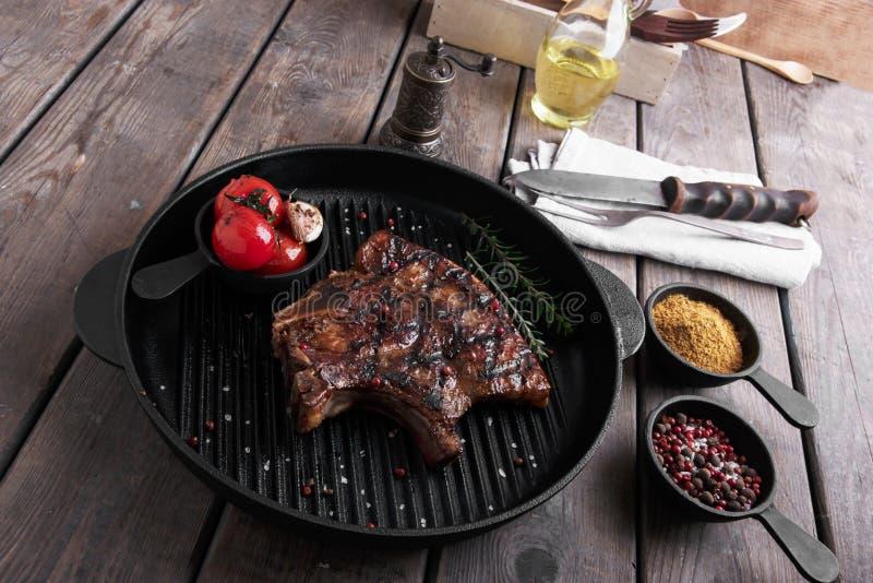 Disossi la bistecca su una griglia con le verdure sulla tavola fotografia stock libera da diritti