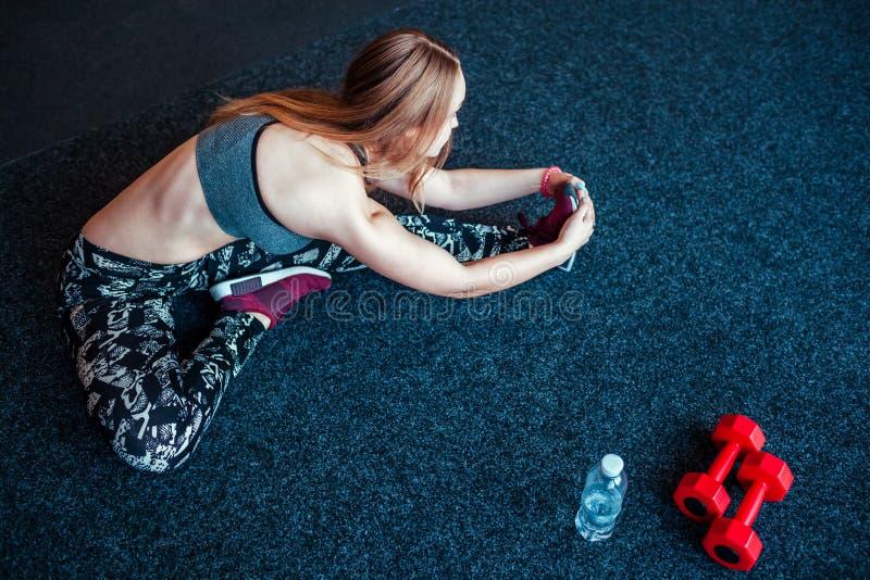 Disparado da jovem mulher que estica no gym Fêmea muscular que faz exercícios para esticar seu corpo no assoalho imagem de stock royalty free