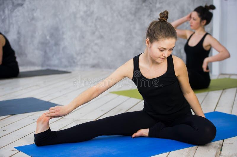 Disparado das jovens mulheres que aquecem-se antes da sessão da ioga Os jovens que sentam-se na esteira do exercício na ioga clas fotos de stock royalty free