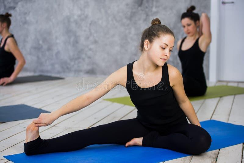 Disparado das jovens mulheres que aquecem-se antes da sessão da ioga Os jovens que sentam-se na esteira do exercício na ioga clas imagens de stock royalty free