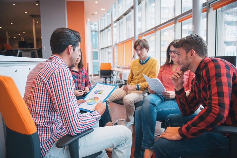 Disparado de um grupo de profissionais novos do negócio que têm uma reunião foto de stock royalty free