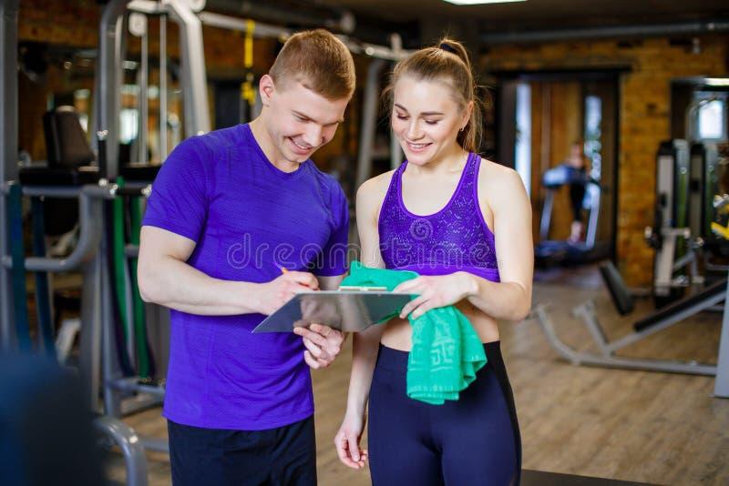 Disparado de um instrutor pessoal que ajuda um membro do gym com seu plano do exercício imagens de stock