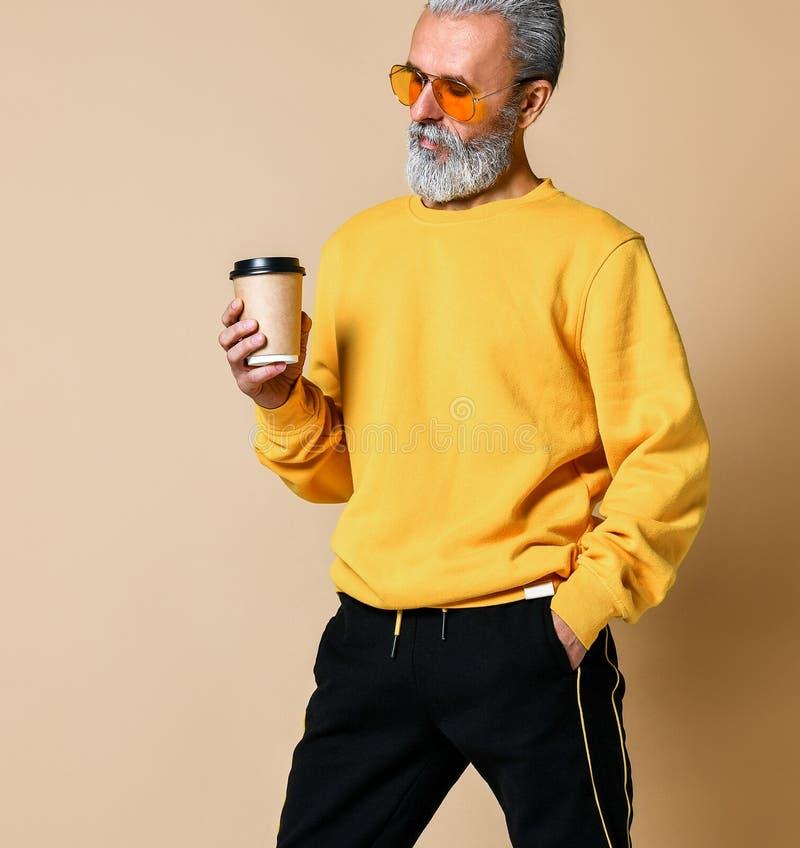 Disparado de um sênior alegre que guarda um copo de café branco e que olha afastado a câmera fotografia de stock