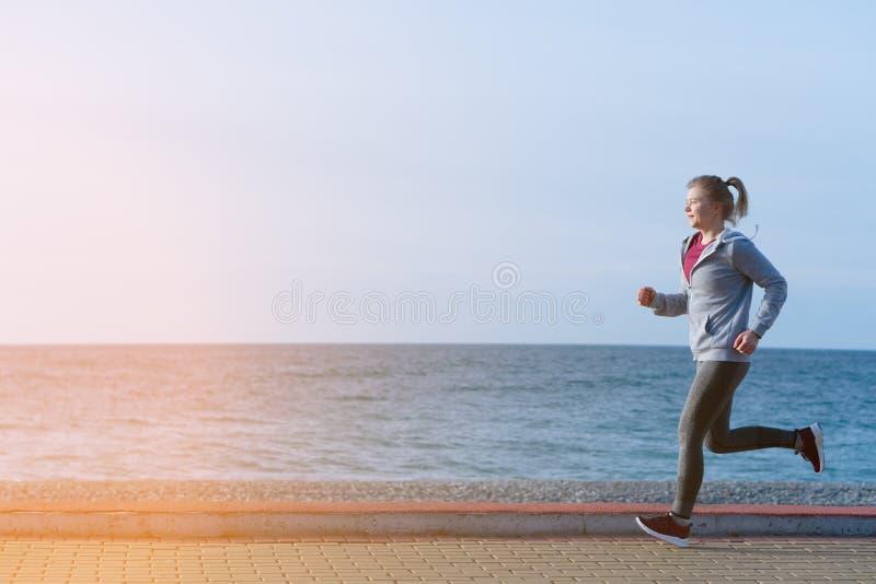 Disparado de um treinamento atlético bonito da mulher no nascer do sol imagem de stock