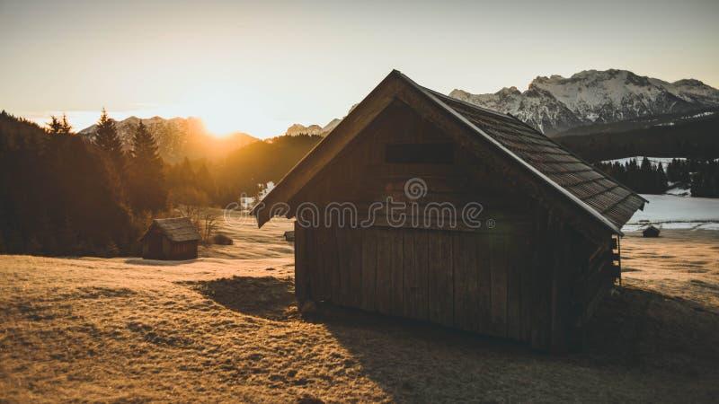 Disparado de uma casa de madeira pequena com grama seca em torno dela durante o por do sol com as montanhas no backgro imagens de stock