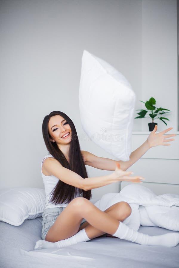 Disparado de uma jovem mulher que senta-se em uma cama imagem de stock royalty free