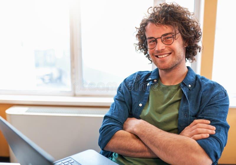 Disparado dentro do homem novo feliz que sorri e que trabalha no computador no local de trabalho moderno contra a janela fotografia de stock royalty free