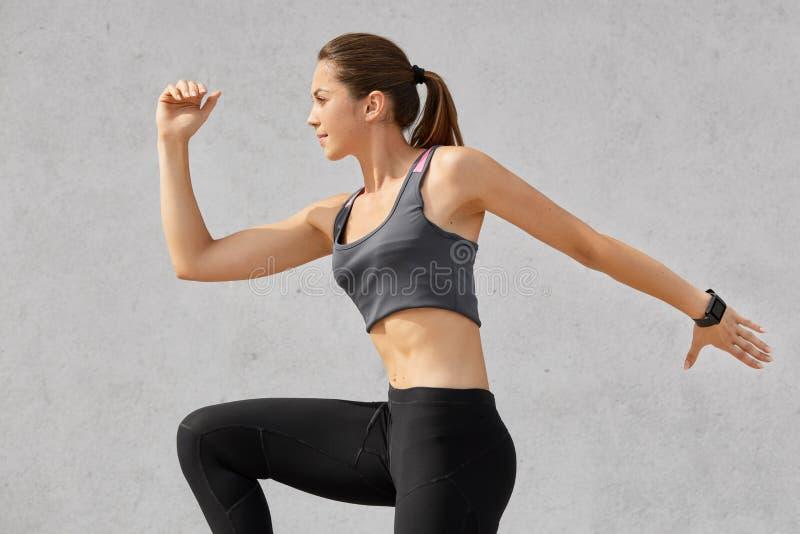 Disparado lateralmente da mulher ativa estar no movimento, tem a cauda de pônei, veste sportsclothes, levanta contra o fundo cinz fotos de stock