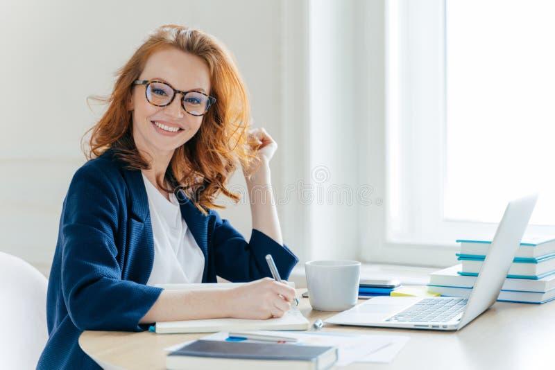Disparado lateralmente da mulher de negócios próspera com cabelo foxy, sorrisos positivamente, informação de registros no bloco d fotografia de stock