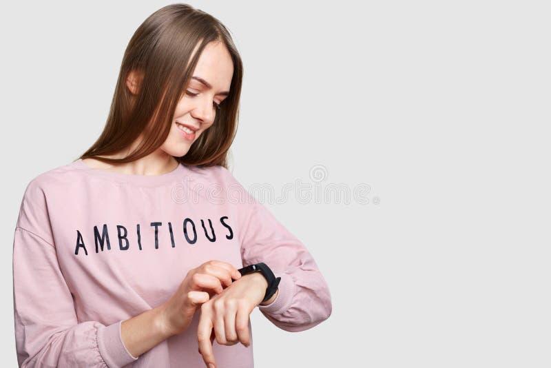 Disparado lateralmente do tempo fêmea atrativo das verificações no relógio de pulso, veste a ligação em ponte ocasional, espera a fotos de stock royalty free