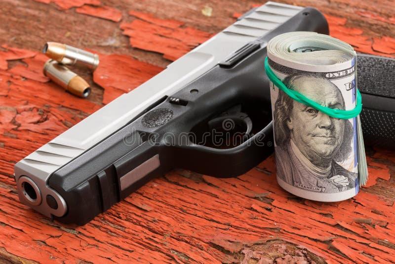 Dispare contra con un rollo de 100 billetes de banco del dólar foto de archivo