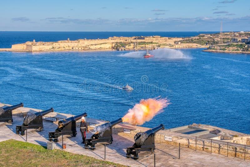 Disparos de cañón al mediodía en un saludo a la batería en el jardín superior de Barrakka, Malta imagen de archivo