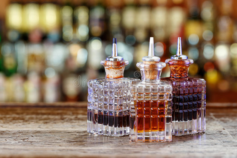 Dispensers for syrups. Inventory of the bartender at the bar counter - droppers for bitters and syrups stand in a row on a blurred background of the bar stock photography