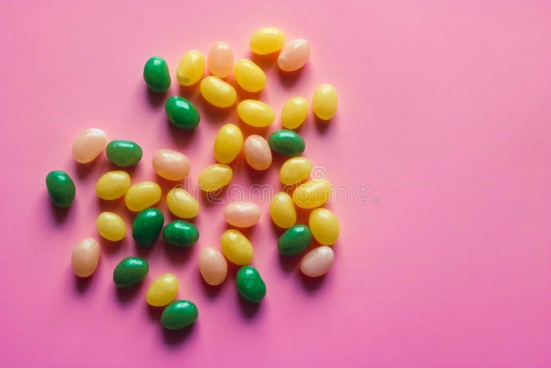 Dispersión de los caramelos multicolores en el fondo rosado Espacio libre para el texto foto de archivo libre de regalías