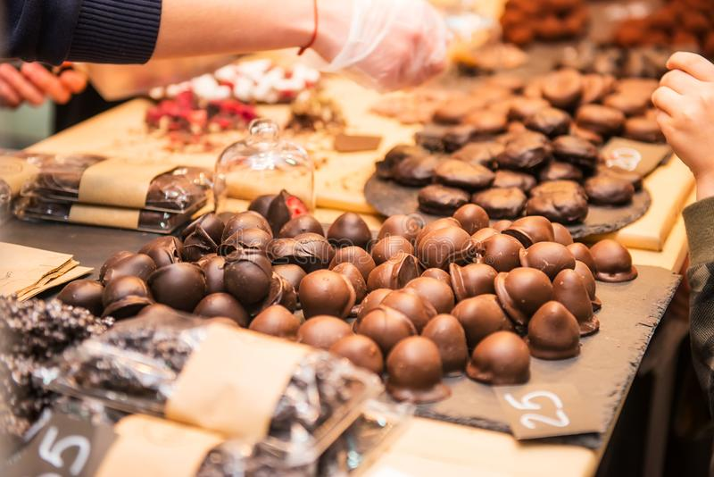 Display with assortment of dark and brown chocolate candies with different fillings. Seller`s hand picks some slice for buyer tes royalty free stock image