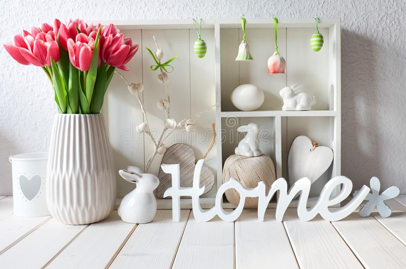 Display cabinet with different objects and pink tulips, wooden w stock images