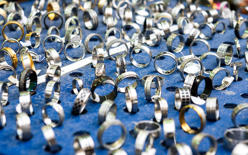 Display with different designs of handmade silver rings on blue stock images