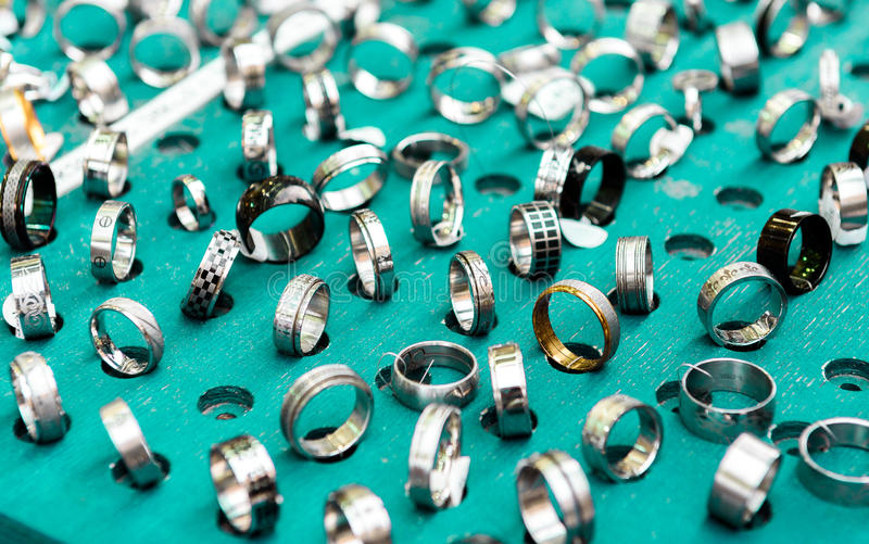 Display with different designs of handmade silver rings on green stock photo