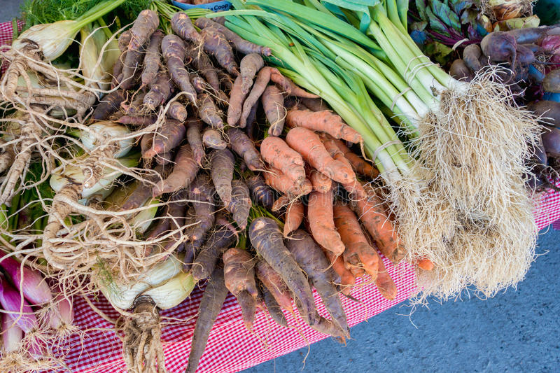 Display of leek and rare heirloom carrots at the local food mark stock photography