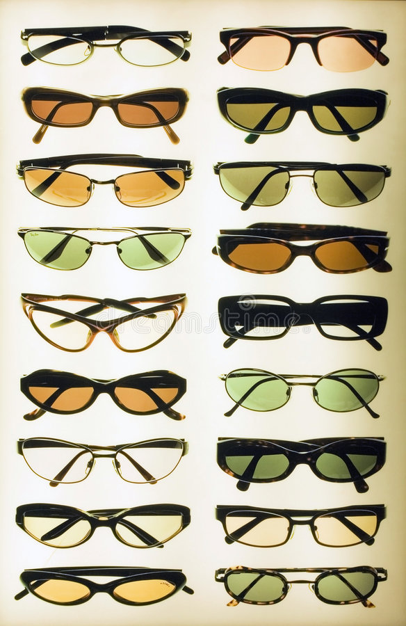 Display of sunglasses. A view of a rack or display of various styles and shades of sunglasses on a white background royalty free stock photos