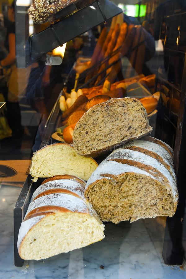 Display window of a bakery and pastry shop. Assortment of different kinds of freshly baked artisan bread rye whole wheat loaves royalty free stock photos